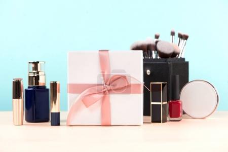 Photo pour Maquillage cosmétiques et boîte de cadeau sur la table en bois. Poser de plat. Vue de dessus - image libre de droit