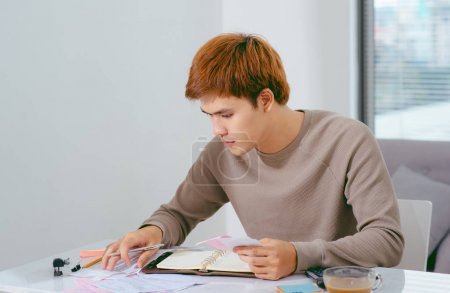 Young Asian man sitting on sofa at table with open notebook and pen