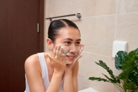 Young beautiful asian woman washing her face with hands by soap