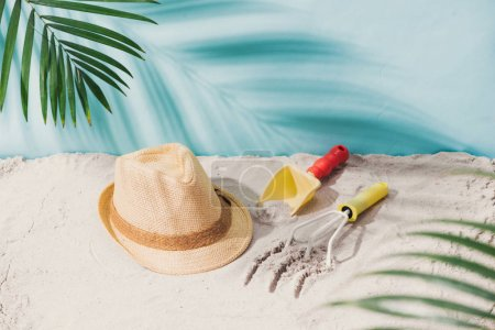 close-up photo of beach hat on sand with toys. Summer concept.