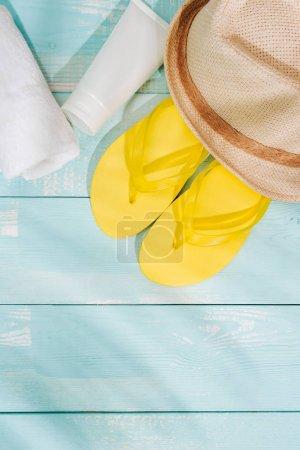Summer background. Beach accessories flip flops, sunglasses, hat and orange juice on wooden deck