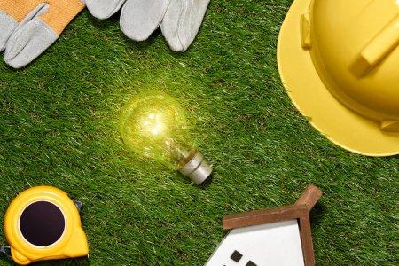 Photo pour Bâtiment vert et concept d'économie d'énergie : projet de maison et outils de travail sur l'herbe - image libre de droit