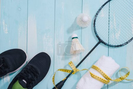 Top view of sport shoes, towel, badminton racket and shuttlecock