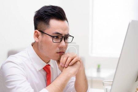 Photo pour Jeune ouvrier élégant au bureau travaillant avec un ordinateur et réfléchissant à la façon de résoudre une tâche difficile - image libre de droit