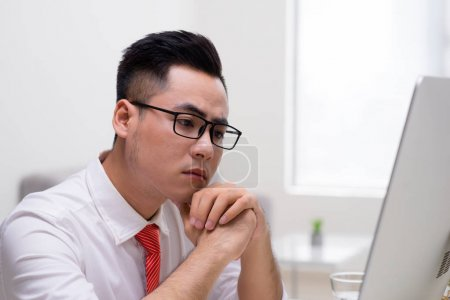 Photo pour Jeune travailleur élégant au bureau de travail avec ordinateur et comment résoudre la difficile tâche de la pensée - image libre de droit