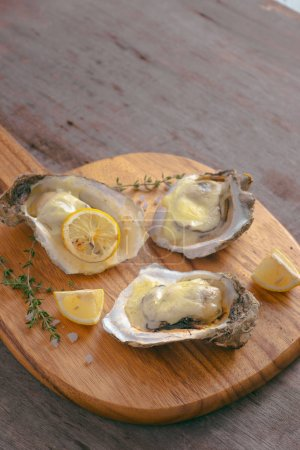 Photo for Tasty fresh oysters with sliced lemon on cutting board. Aphrodisiac food for increasing sexual desire - Royalty Free Image