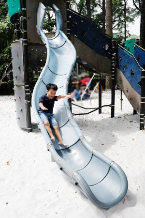Photo for Ho Chi Minh City, Vietnam - October 25, 2017: Active boy sliding down in public playground - Royalty Free Image