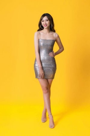 Photo for Beautiful female posing in long silver party dress over yellow background - Royalty Free Image
