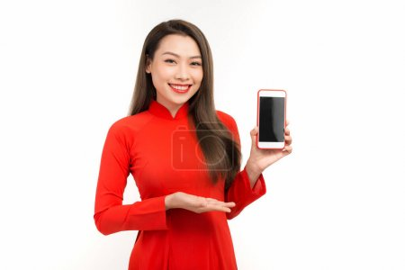 Photo for Attractive woman in ao dai dress showing screen mobile phone, isolated on white background - Royalty Free Image