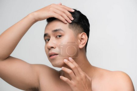 Photo for Portrait of shirtless young handsome Asian man checking his face for skin care and beauty concepts - Royalty Free Image