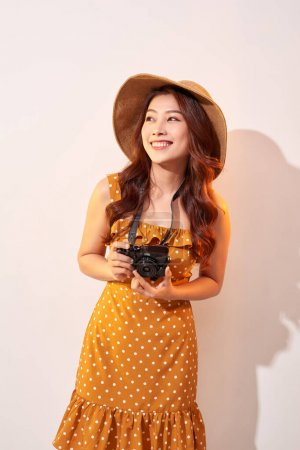 Photo for Portrait of cheerful smiling young woman taking photo with inspiration and wearing summer dress. Girl holding retro camera. Model posing on beige background in hat - Royalty Free Image
