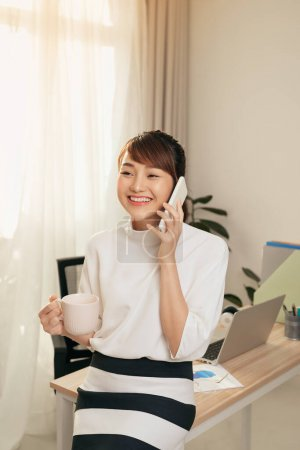 Photo for Cheerful Asian woman having conversation on mobile phone and drining coffee at office - Royalty Free Image