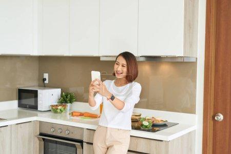 Photo pour Verticale de femme au foyer asiatique de sourire faisant le selfie dans la cuisine domestique - image libre de droit