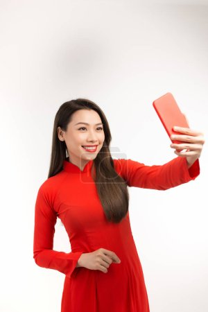 Photo for Asian beautiful girl dressed in Vietnamese national costume is taking pictures with the camera from the smartphone - Royalty Free Image