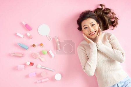 Photo pour Belle femme asiatique souriante allongée sur le sol rose avec ses outils de maquillage cosmétiques. Vue en haut - image libre de droit