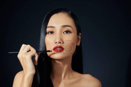 Photo pour Jeune femme, appliquer le rouge à lèvres avec un applicateur - image libre de droit