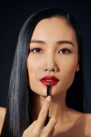 Photo pour Belle femme peint les lèvres rouge à lèvres. Visage de belle femme. Détail de maquillage. Fille de beauté avec une peau parfaite. - image libre de droit