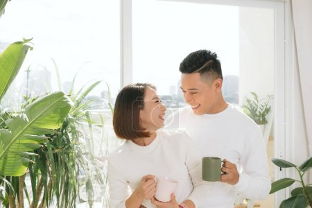 Happy Asian Lover kissing and hugging which holding a cup of wat