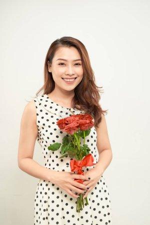 Photo pour Belle femme tenant un bouquet de roses. Sourire et regarder la caméra. Vue de face - image libre de droit