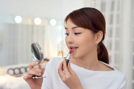 Photo pour Une jeune femme asiatique souriante qui applique un rouge à lèvres et regarde le miroir. - image libre de droit