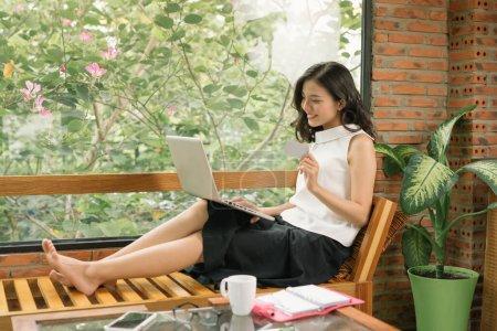 Photo pour Portrait d'une fille tenant une carte de crédit et utilisant un ordinateur portable. Achats en ligne - image libre de droit