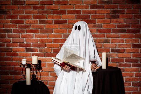 Ghost holding book and wine over brick background. Halloween party.