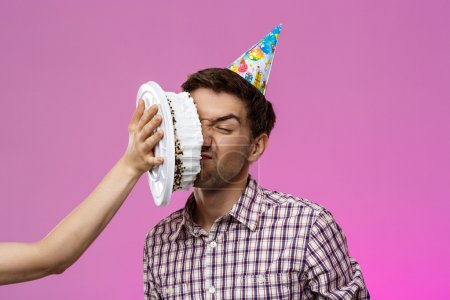 Man with cake on face over purple background. Birthday party.