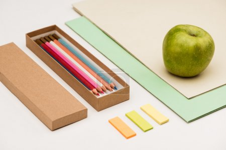Stationery, apple on white table. Office stuff.