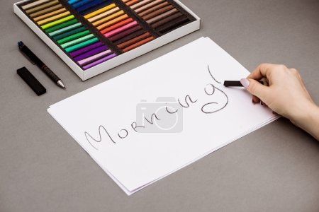 Girls hand writing word morning on paper with pastel.