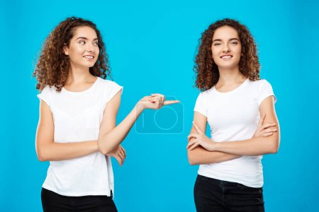 Girl pointing finger at her sister twin over blue background.