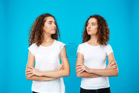 Two girls twins posing with crossed arms over blue background.