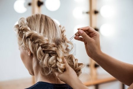 Female hairdresser making hairstyle to blonde girl in beauty salon.