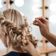 Female hairdresser making hairstyle to beautiful b...