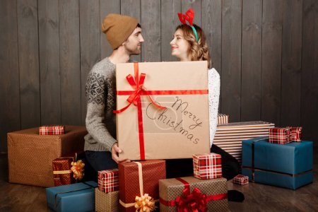 Young couple sitting among christmas gift boxes over wooden background.
