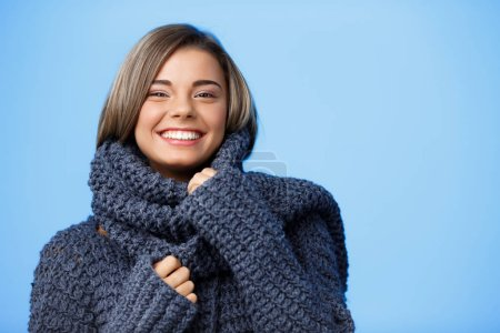 Young beautiful fair-haired girl in hat and sweater smiling looking at camera over blue background.