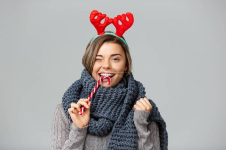 Young beautiful fair-haired girl in large knited scarf and christmas reindeer antlers smiling eating striped lollypop over grey background.