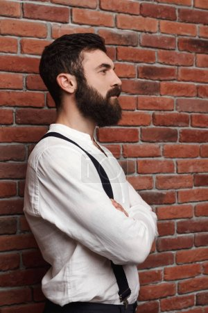 Young handsome man posing with crossed arms over brick background.