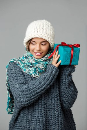 Young beautiful fair-haired girl in knited hat sweater and scarf smiling holding gift box over grey background.