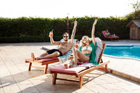 Friends smiling, drinking cocktails, lying on chaises near swimming pool.