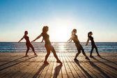 Silhouettes of sportive girls dancing near sea at sunrise.