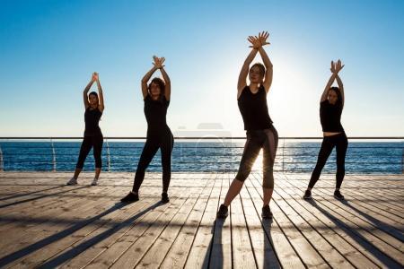 Silhouettes of sportive girls dancing sport near sea at sunrise.