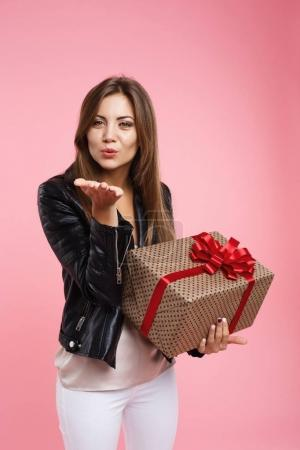 Charming long haired woman blowing kiss looking straight, holding present