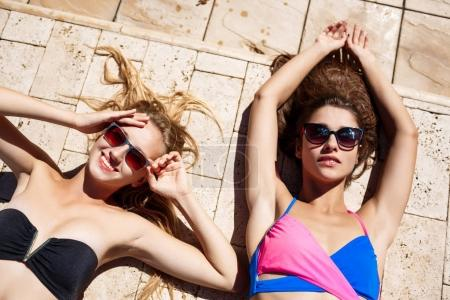 Young beautiful girls smiling, sunbathing, relaxing near swimming pool.