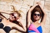 Young beautiful girls smiling, sunbathing, relaxing near swimming pool.