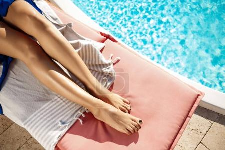 Girl lying on chaise near swimming pool. Close up of legs.