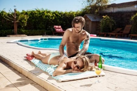 Handsome man applying suntan cream on  girl near swimming pool.