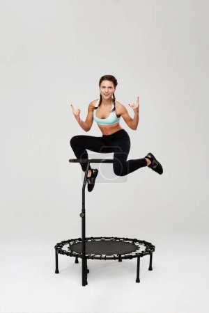 Sporty girl training on rebounder and showig rock sign