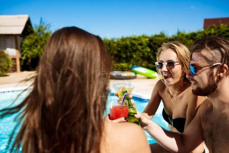 Friends speaking, smiling, drinking cocktails, resting, relaxing near swimming pool.
