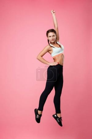 Sporty woman jumping up making fun isolated on pink background