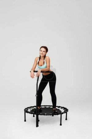 Slim young woman with bunches stying on rebounder after training